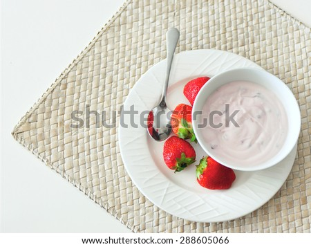 Sweet strawberry berries served with fresh organic yoghurt in a white bowl on a wickered rug on the table. Fresh fruit dessert for the breakfast. Top view, copy space - stock photo
