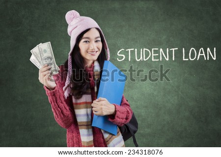 Sweet student girl wearing a knitted clothes and holding money dollars in the classroom - stock photo