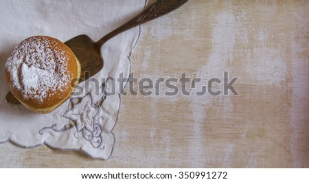 Sweet sugary donut on vintage handmade napkin, retro overhead shot on wooden table with lot of copy space
