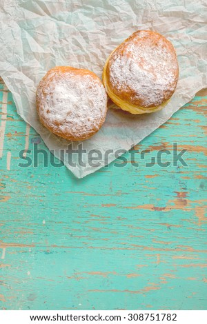 Sweet sugary donuts on rustic wooden kitchen table, top view of tasty bakery doughnuts in vintage retro toned overhead shot - stock photo