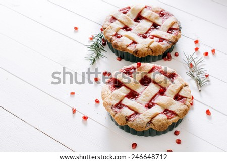 Sweet tart cake stuffed with pomegranate jam on wooden background with blank space  - stock photo