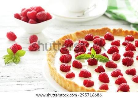 Sweet tart cake with raspberries on white wooden background
