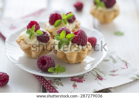 Sweet tartalette with pastry cream, fresh raspberries and mint - stock photo