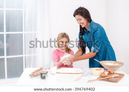 Sweet time of family cooking. Mother and daughter having fun while preparing meal. Nice white interior. Mother and daughter kneading the dough - stock photo