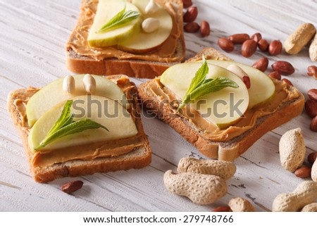 sweet toast with fresh apple and peanut butter on the table. Horizontal  - stock photo