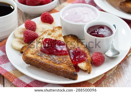 sweet toasts with fresh raspberry, jam and yoghurt for breakfast, close-up - stock photo