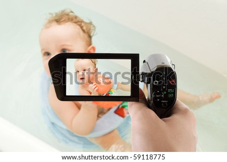 sweet toddler baby boy in bath with ball on camcorder - stock photo