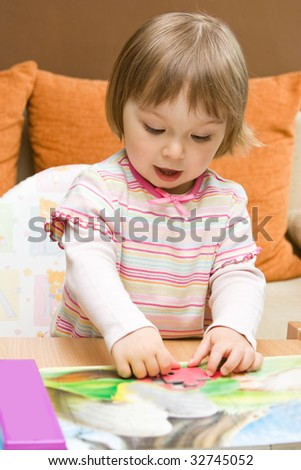 sweet toddler baby girl playing puzzle