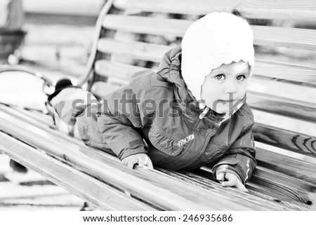 sweet toddler girl is on the bench  - stock photo