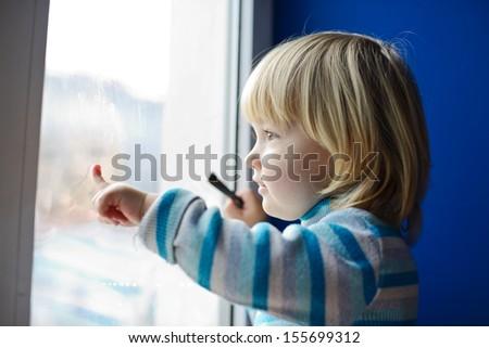 sweet  toddler girl looking through the window - stock photo
