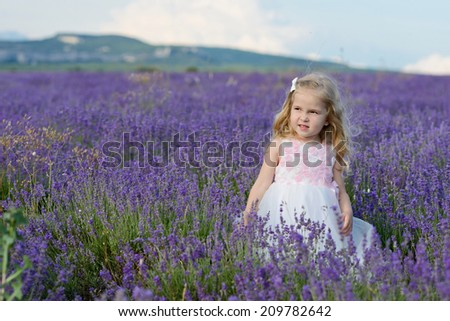 sweet toddler girl standing in lavender field - stock photo
