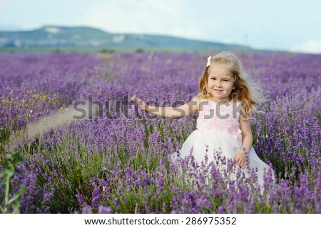 sweet toddler girl walking in lavender field - stock photo