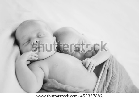 sweet twins are sleeping and hugging in soft focus