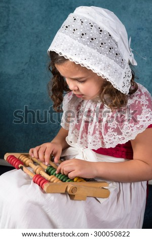 Sweet victorian girl posing in the old style with an abacus - stock photo