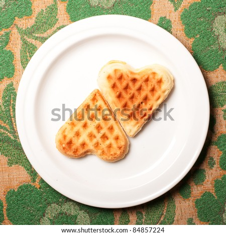 sweet wafer heart on dish, on retro background - stock photo