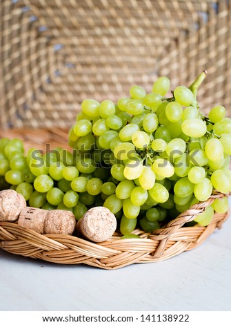 sweet white grapes in a basket on the table. A glass of white wine