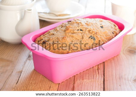 Sweet whole-wheat bread with bananas, nuts and raisins in silicone bakeware on wooden background - stock photo