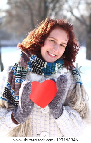 Sweet winter romantic girl holding a red heart - stock photo