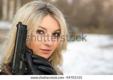 Sweet woman with a weapon in winter forest - stock photo