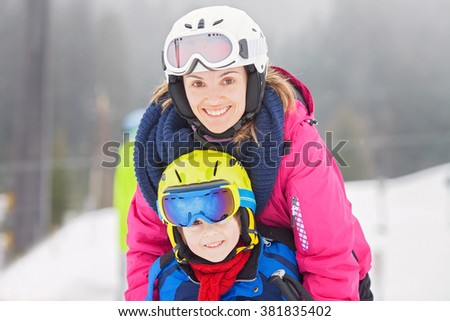Sweet young boy and his mother, learning to ski on a mild ski slope in Austrian ski resort on a cloudy day - stock photo
