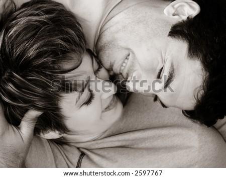 Sweet young couple lying on the rug - stock photo
