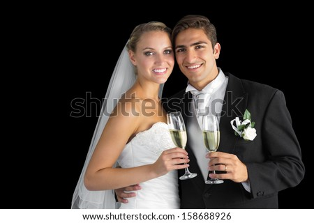 Sweet young couple posing with champagne glasses smiling at camera - stock photo