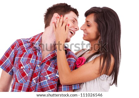 Sweet young couple preparing to kiss. Girl is caressing his face and they are both smiling