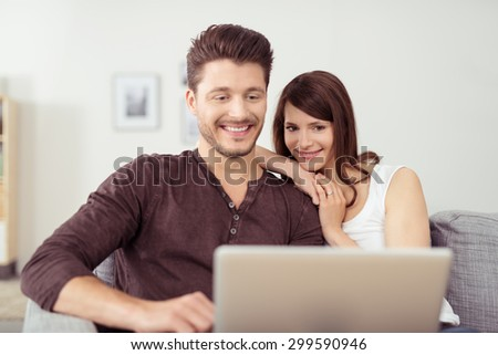 Sweet Young Couple Relaxing at the Living Room, Watching Something on Laptop Computer Together with Happy Facial Expressions. - stock photo