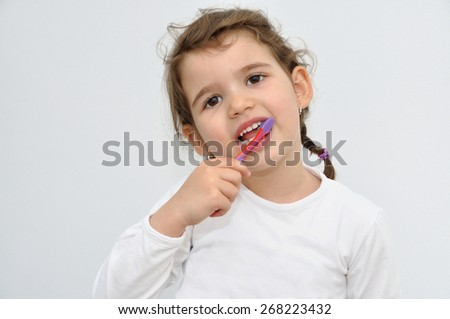 Sweet young girl with pigtail brushing the beautiful white teeth with toothbrush - stock photo
