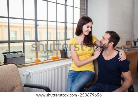 Sweet Young Lovers Looking Each Other While Resting at the Living Room. - stock photo