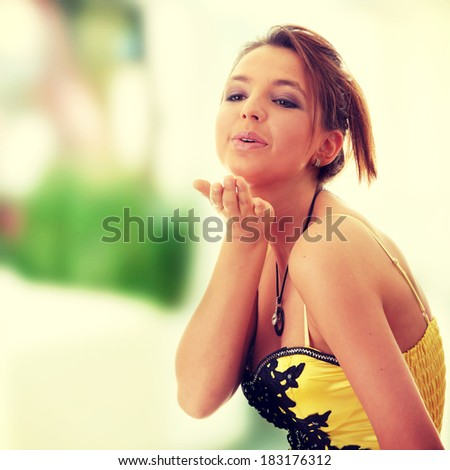 Sweet young woman (teenage girl) in yellow/black dress sending a kiss - stock photo