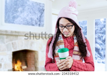 Sweet young woman wearing winter knitted clothes and enjoy hot drink in a disposable cup at home - stock photo