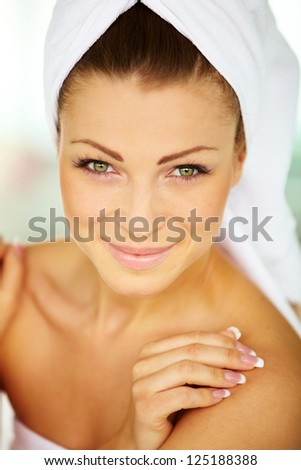Sweet young woman wrapped in towel with hands on her body