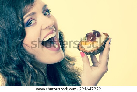 Sweetness and happiness concept. Closeup cute woman curly hair eating fruit cake cupcake face profile yellow background - stock photo