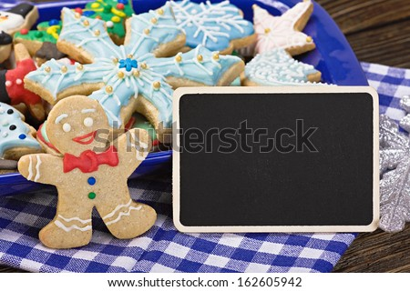 sweets and biscuits for Christmas and a blackboard with a greeting for the holiday - stock photo