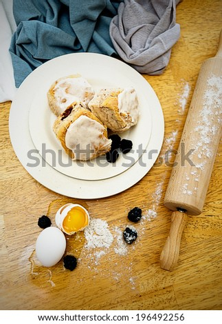Sweets on a white plate next to a rolling pin. - stock photo