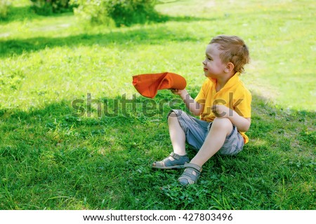 swelter. sweaty kid sitting in the shadows. boy fanning herself with hat to cool off - stock photo