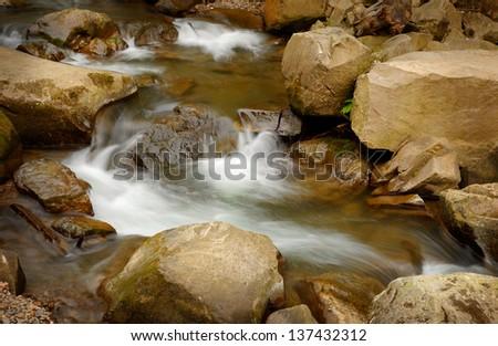 swift stream running between stones - stock photo