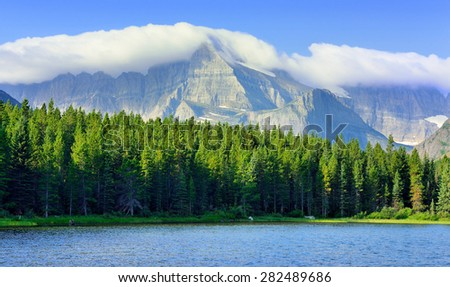 Swiftcurrent lake in high alpine landscape on the Grinnell Glacier trail, Glacier national park, Montana in summer - stock photo