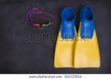 Swim fins and goggles on a blackboard or chalkboard for high school swim team background or competitive swim teams.  - stock photo