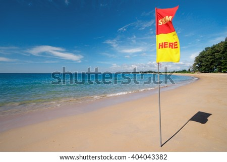 Swim here, Safety flag on the sea beach. - stock photo
