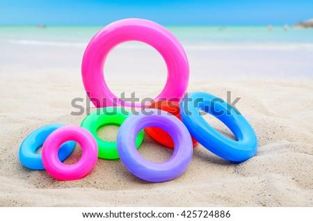 Swim rings on beach background - stock photo