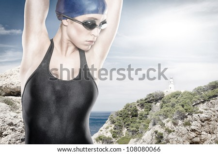 Swimmer in front of a lighthouse - stock photo
