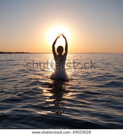 Swimmer jumping out of sea water on warm sunrise