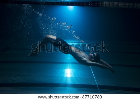Swimmer swimming underwater exhaling bubbles on blue background - stock photo
