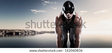 Swimmer triathlon muscled man with cap and glasses outdoor at a lake with blue cloudy sky. Extreme fitness sport.