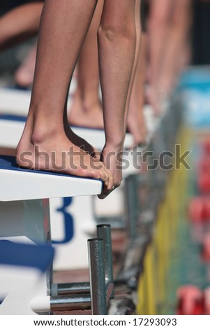 Swimmers on starting blocks ready to dive into water with only hands and feet showing - stock photo
