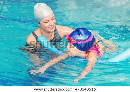 Swimming class - little girl learning to swim with swimming instructor