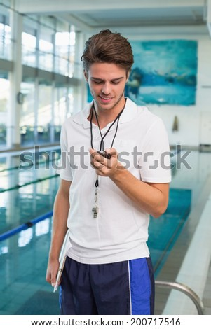 Swimming coach looking at his stopwatch by the pool at the leisure center - stock photo