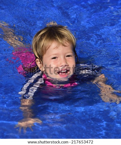 Swimming lessons: Cute baby girl is learning how to swim in the pool - stock photo